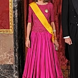 Wearing a Three-Quarter-Sleeved Shimmery Bodice and Pleated Fuchsia Gown