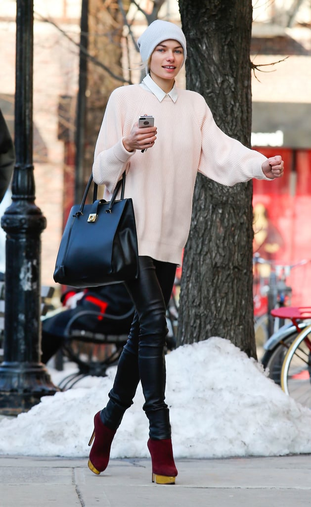 Jessica Hart layered up in a collared blouse, a soft pink sweater, leather pants, Charlotte Olympia booties, a black Salvatore Ferragamo bag, and a cozy beanie in NYC.