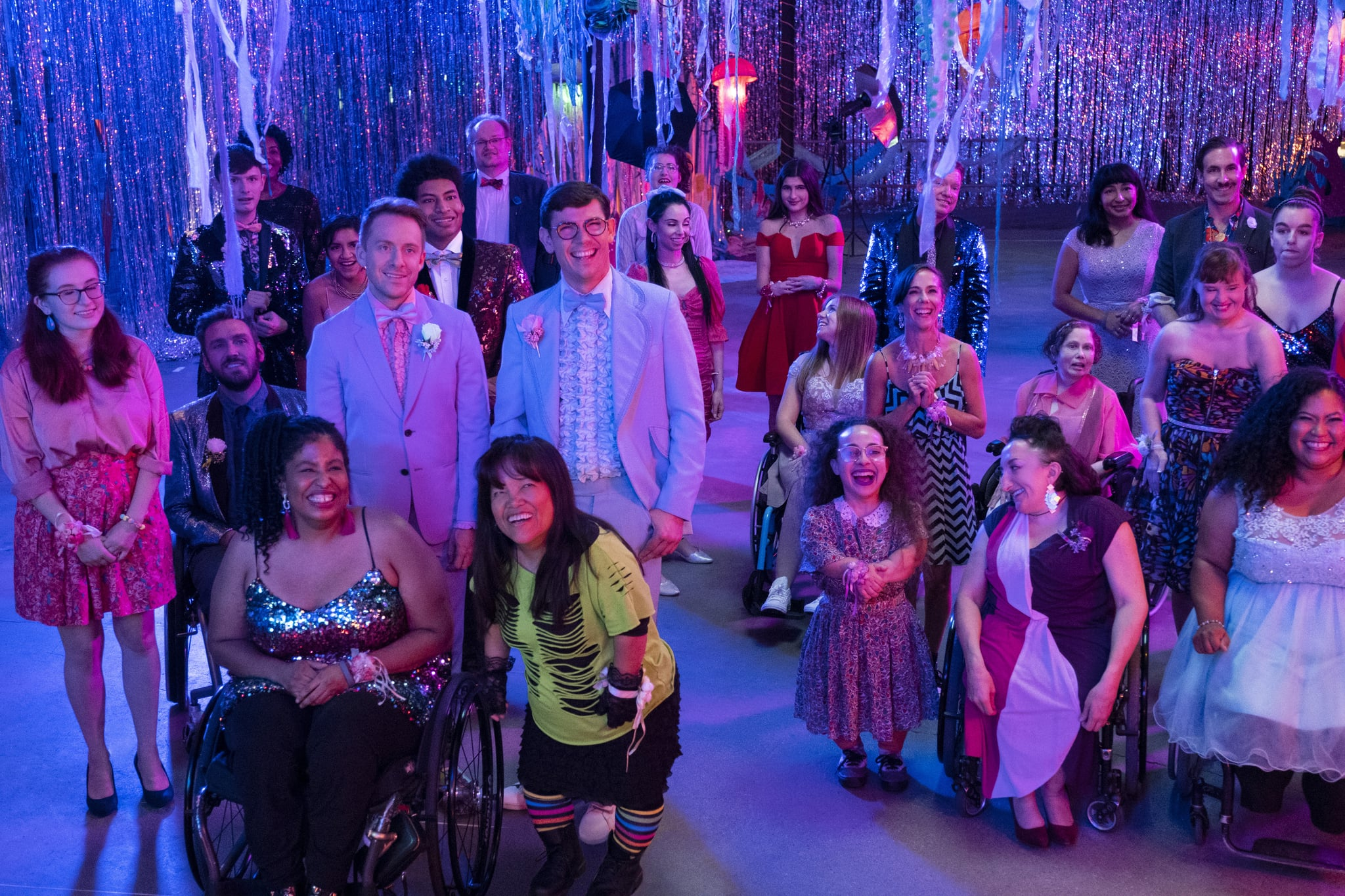 Two men in light blue tuxedos are standing in a room decorated for a party, with festive streamers hanging from the ceiling and walls. They are surrounded by men and women dressed mostly in party dresses and suits. Some of the men and women use a wheelchair, and some are people of short stature.