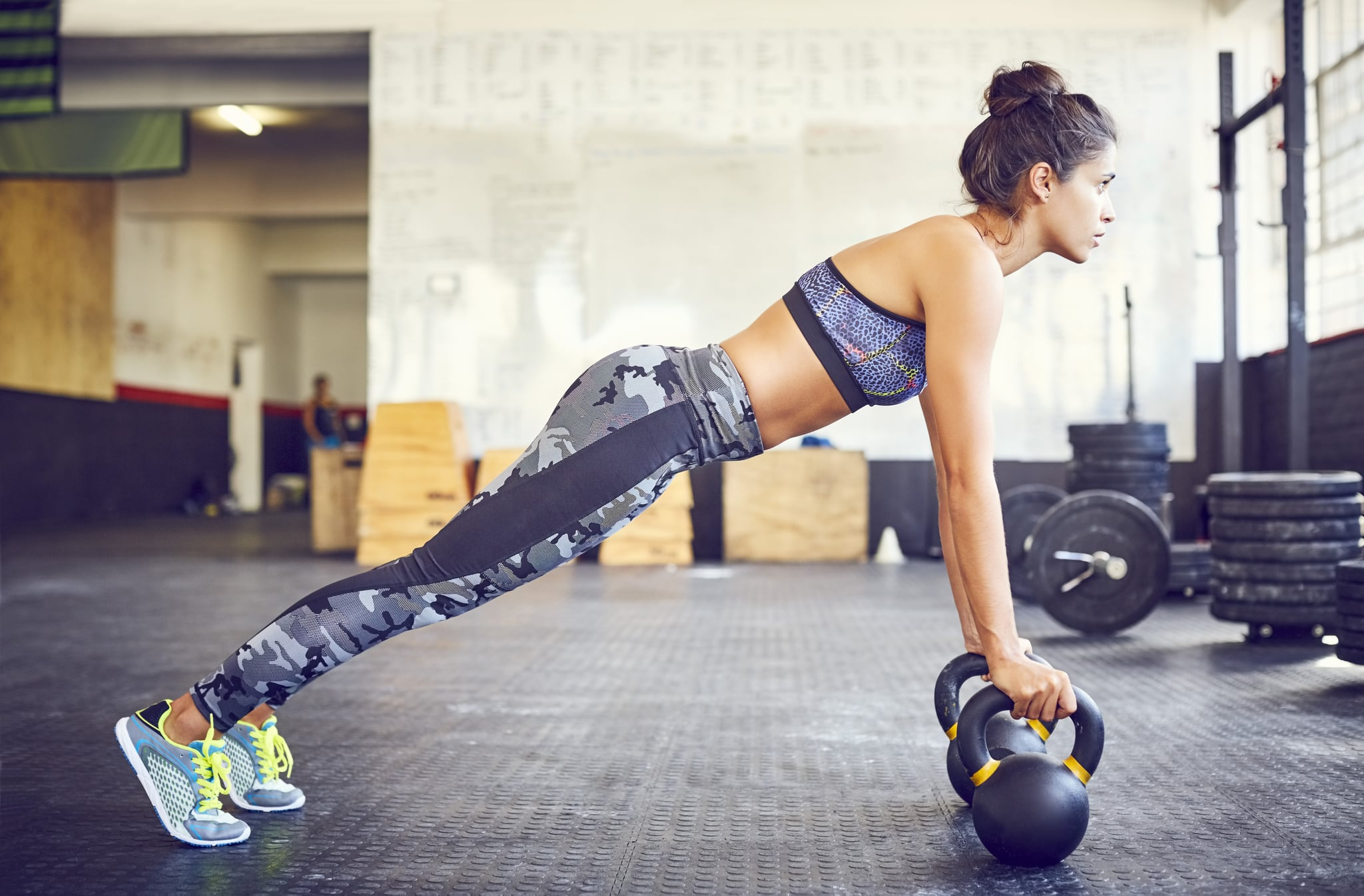 Determined fit athlete doing push-ups on kettlebells. Side view of woman exercising in gym. Sporty female in health club.