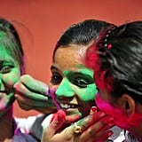 Girls played with colored powder outside a school in Allahabad, India.