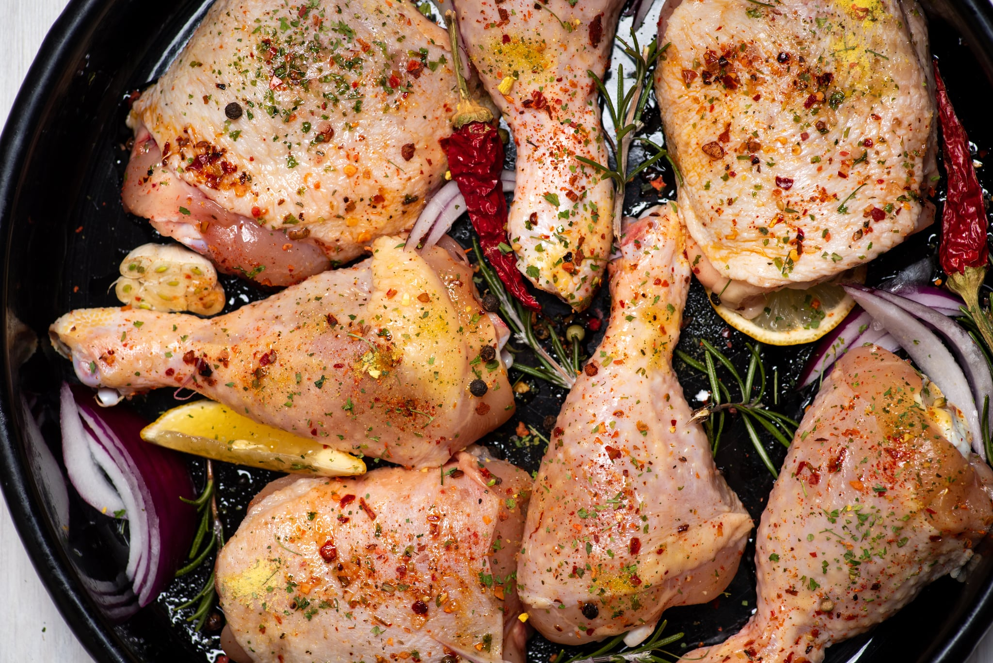 Raw uncooked chicken legs marinated with with spices and ingredients ready for cooking