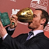 Michael Fassbender plays with his new cup.