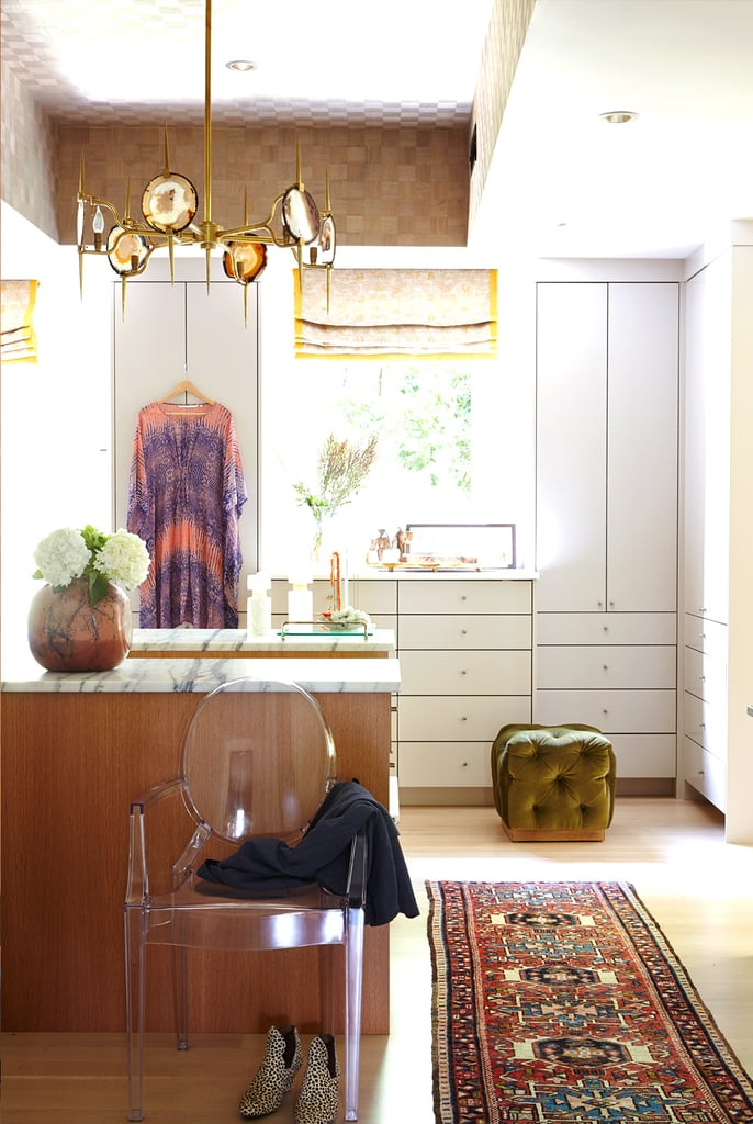The master suite's closet is actually more of a dressing room and, not surprisingly, Baylin's prized space. Patterned wallpaper, wood-veneer detailing, and an agate-slice chandelier exude bohemian glamour.