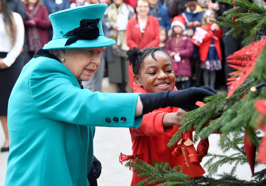 The British royal family is certainly getting into the holiday spirit. Prince William and Kate Middleton recently hosted a Christmas party for military families, Prince Harry and Meghan Markle attended their first Christmas carol service, and now Queen Elizabeth II is spreading cheer with her latest appearance in London. On Wednesday, the queen visited Coram, the UK's oldest children's charity, to open a new center in her name and partook in a sweet holiday tradition in the process.  The royal shared a cute moment with a little girl as she hung her very own ornament on a Christmas tree. During her visit, she also met the oldest surviving resident from The Foundling Hospital, the original name of Coram. The 102-year-old man named Edward Newton actually met the queen's late father, King George, during a visit in 1926 when he was just a little boy. What a small world!       Related:                                                                                                           12 British Royal Christmas Traditions That Will Surprise You