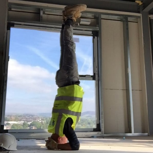 Man Doing Yoga at Work on a Building Site