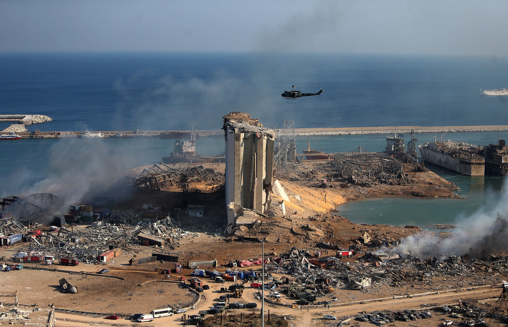 TOPSHOT - A general view shows the damaged grain silos of Beirut's harbour and its surroundings on August 5, 2020, one day after a powerful twin explosion tore through Lebanon's capital, resulting from the ignition of a huge depot of ammonium nitrate at the city's main port. - Rescuers searched for survivors in Beirut after a cataclysmic explosion at the port sowed devastation across entire neighbourhoods, killing more than 100 people, wounding thousands and plunging Lebanon deeper into crisis. The blast, which appeared to have been caused by a fire igniting 2,750 tonnes of ammonium nitrate left unsecured in a warehouse, was felt as far away as Cyprus, some 150 miles (240 kilometres) to the northwest. (Photo by STR / AFP) (Photo by STR/AFP via Getty Images)