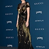 Perhaps getting prepared for her provocative role in the upcoming Fifty Shades of Grey, Dakota Johnson wore an immaculate gold-and-black Gucci dress, with the same sheer construction and feather detailing as Valletta's top.
