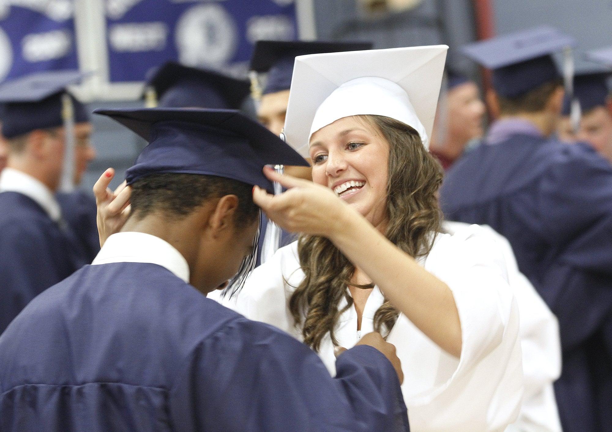 Westbrook High School Graduation. Kaelyn Galipeau helps classmate Jeremiah Steele with his cap before the start of graduation ceremonies. Photographed on Friday, June 8, 2012.  (Photo by Derek Davis/Portland Press Herald via Getty Images)