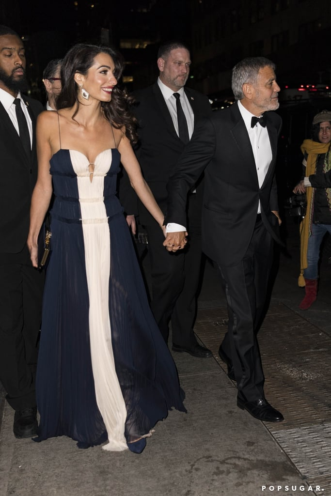 Amal Clooney is proving once again that she's a badass in every element of her life. The human rights lawyer stepped out with her husband George Clooney recently to attend the 70th anniversary of the UN Correspondents Association in New York City, and naturally, she chose a dress that radiated elegance and grace.  She opted for a stunning navy and white floor-length J. Mendel gown with a sweetheart neckline as she accepted the 2018 UNCA Global Citizen of the Year Award. George looked suave as ever in a tux to complement her glamorous ensemble. She paired the gown with dramatic dangling earrings, navy pointed shoes, and a matching clutch. Ahead, see more snaps of her night-out look, and then learn the secret to how her outfits are always so good.      Related:                                                                                                           Amal Clooney's Best Outfits of the Year Could Last Us a Whole Lifetime