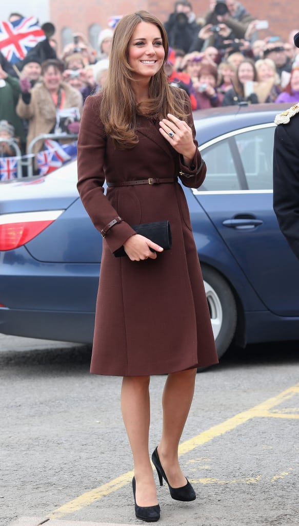 """Kate Middleton wrapped up her baby bump in a brown Hobbs coat yesterday when she arrived at the National Fishing Heritage Center in Grimsby, England. She clutched a gift of white flowers as she waved at the gathered crowd and walked into the Center in black L.K. Bennett pumps. Kate shared that the baby is """"very much so"""" kicking when asked by a fan whether she'd felt movement yet. She may have also let slip the gender of the baby! It's been a busy few days for Kate, who travelled to the Swiss Alps this weekend with Prince William and Prince Harry to attend a friend's wedding and get in a bit of fun on the slopes. Despite her snowy vacation, Kate hasn't been shying away from her royal duties and was last seen making an appearance at Hope House, a rehab center for women, in London. She may have a full schedule of work ahead of her until the Winter — Kate's due in July."""