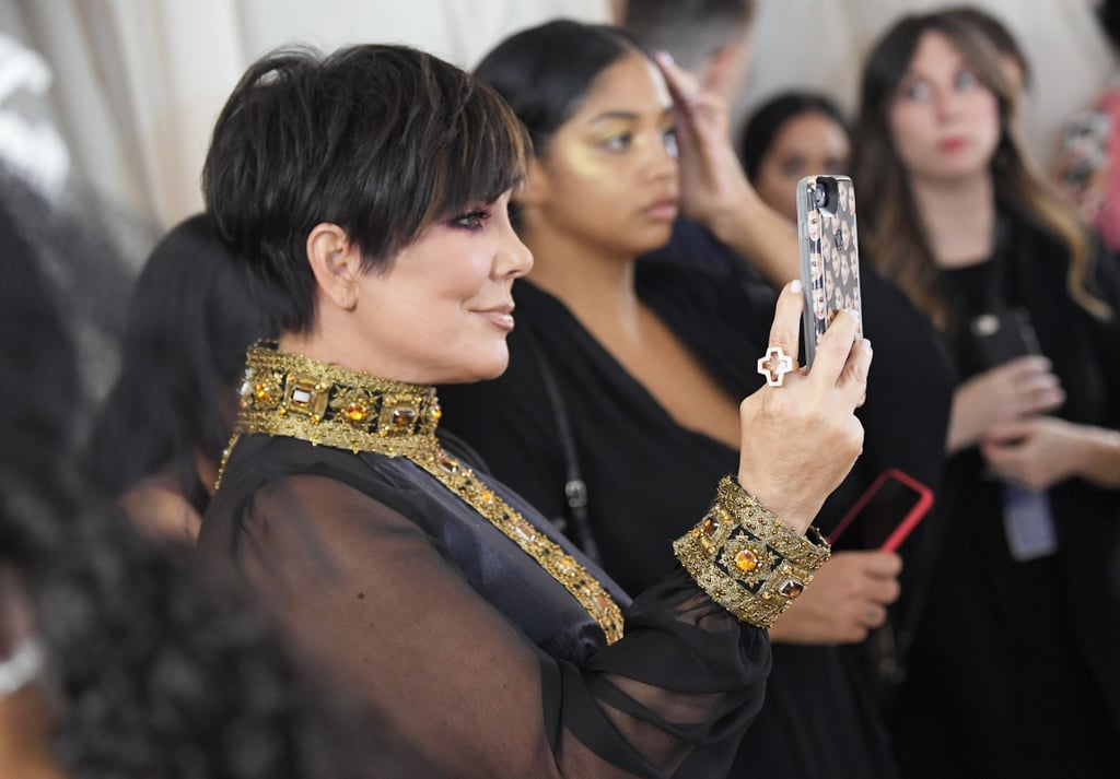 """Is there anything more Kris Jenner than Kris Jenner holding up a Kimoji phone case to take pictures of her daughters at the Met Gala? A momager's work is never done, and in a scene reminiscent of her iconic """"You're doing amazing, sweetie"""" moment from Keeping Up With the Kardashians, Kris snapped pictures of her daughters on the Met Gala red carpet — with the Kimoji Cry Face Case, no less. After walking the red carpet herself and posing for pictures with boyfriend Corey Gamble, she was spotted holding up her cell to capture her daughters' arrivals. While Kylie showed up with Travis Scott, Kim posed solo on the red carpet and Kendall Jenner turned heads in an unexpected look."""
