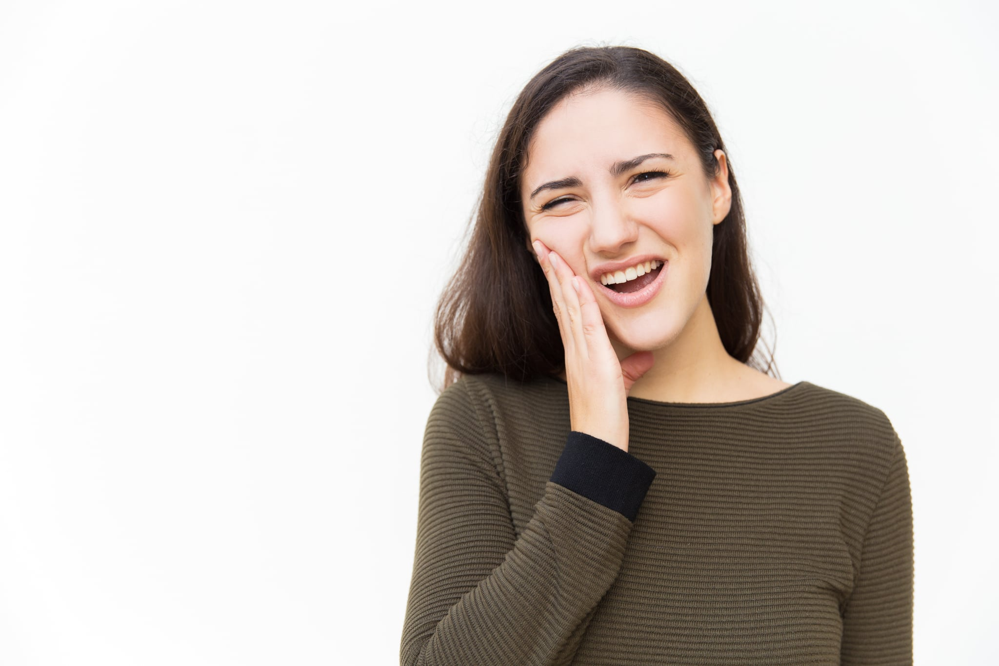 Upset woman with pain grimace suffering from toothache. Young woman in casual standing isolated over white background. Dental problem concept