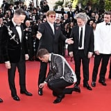 Finally, Taron Adds One Last Touch to Elton's Now Properly Tied Shoe