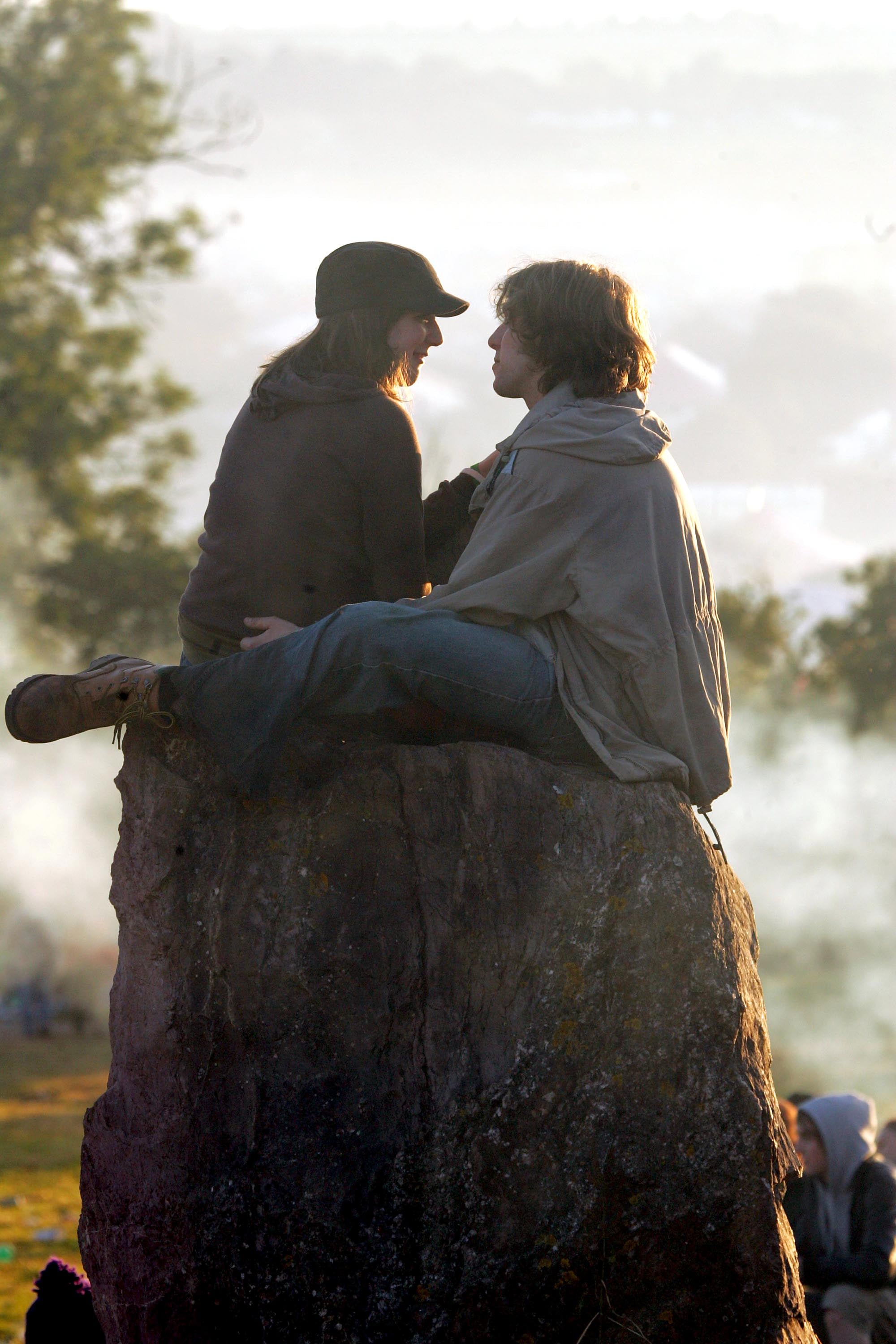 Lovebirds sat at the stone circle at Glastonbury festival in England.