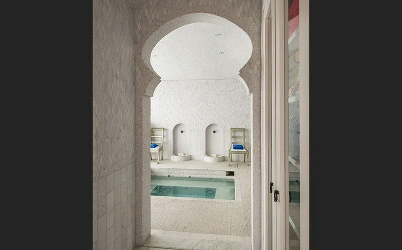 The bathhouse includes stunning details like a Moroccan archway.