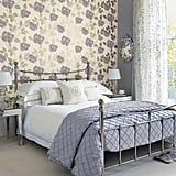 Feminine florals rule this room, so having cohesive mirrored and silver furnishings keeps it from looking too busy. Source