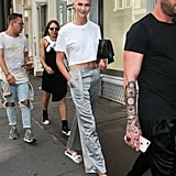 Karlie Was Seen Wearing Gray Silk Trousers and a White Crop Top