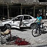 A Syrian boy walks his bike through Douma after an airstrike on the rebel-held territory.