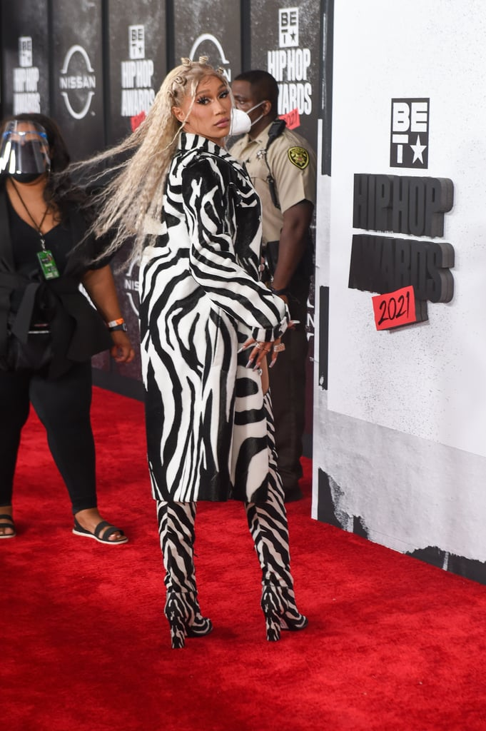 """If my pastel wardrobe suddenly gets replaced by a sea of stripes in black and white, I'll have BIA to thank for her zebra """"camouflage"""" on the red carpet at the 2021 BET Hip Hop Awards. The rapper took the stage on Tuesday in an embellished silver corset during a performance of """"Whole Lotta Money"""" before Lil Jon joined her on stage to sing """"Bia Bia."""" But all the glitz and glam of her stage look did nothing to erase her zebra print Bottega Veneta trench coat from our memories.  The $3,900 coat featured a monochromatic belt with a triangular buckle and a hypnotic wrap-around pattern that would make it easy to get lost in a sea of black and white. But BIA's outfit popped, and her giant layered """"BIA"""" necklace and silver french tip nails only made the look even more eye-catching. From front to back, the coat, layered over a black bodysuit, is mesmerising, but we might be even more obsessed with her matching square-toed, over-the-knee boots. Between the boots and coat, BIA might have us hooked on animal print all over again. Check out her outfit from all angles ahead.      Related:                                                                                                           It's Tommy Dorfman's Fashion Week World, and We're All Just Living in It"""