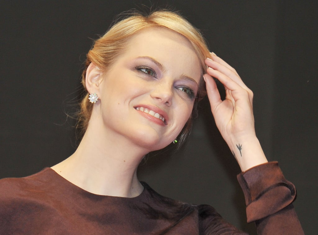 Emma Stone fixed her hair at The Amazing Spider-Man premiere in Japan.