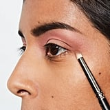 """Using the soft brown shadow in the MAC x Selena collection, No Me Queda Mas Eye Shadow ($17), and a pencil brush, draw a tiny triangle on the outer corner of your eye — from your crease to the top of your lash line. """"Be generous with the product; again, you don't want to create a heavy contrast, but you definitely want to see that change of color into brown in the corner,"""" Chantel said. If you didn't get your hands on the MAC x Selena collection, try Charcoal Brown Eye Shadow ($16)."""
