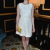 At H&M's Fall 2013 fashion show in Paris, Emma Roberts was pretty in a white fit-and-flare dress, a yellow clutch, and white Christian Louboutin pumps.