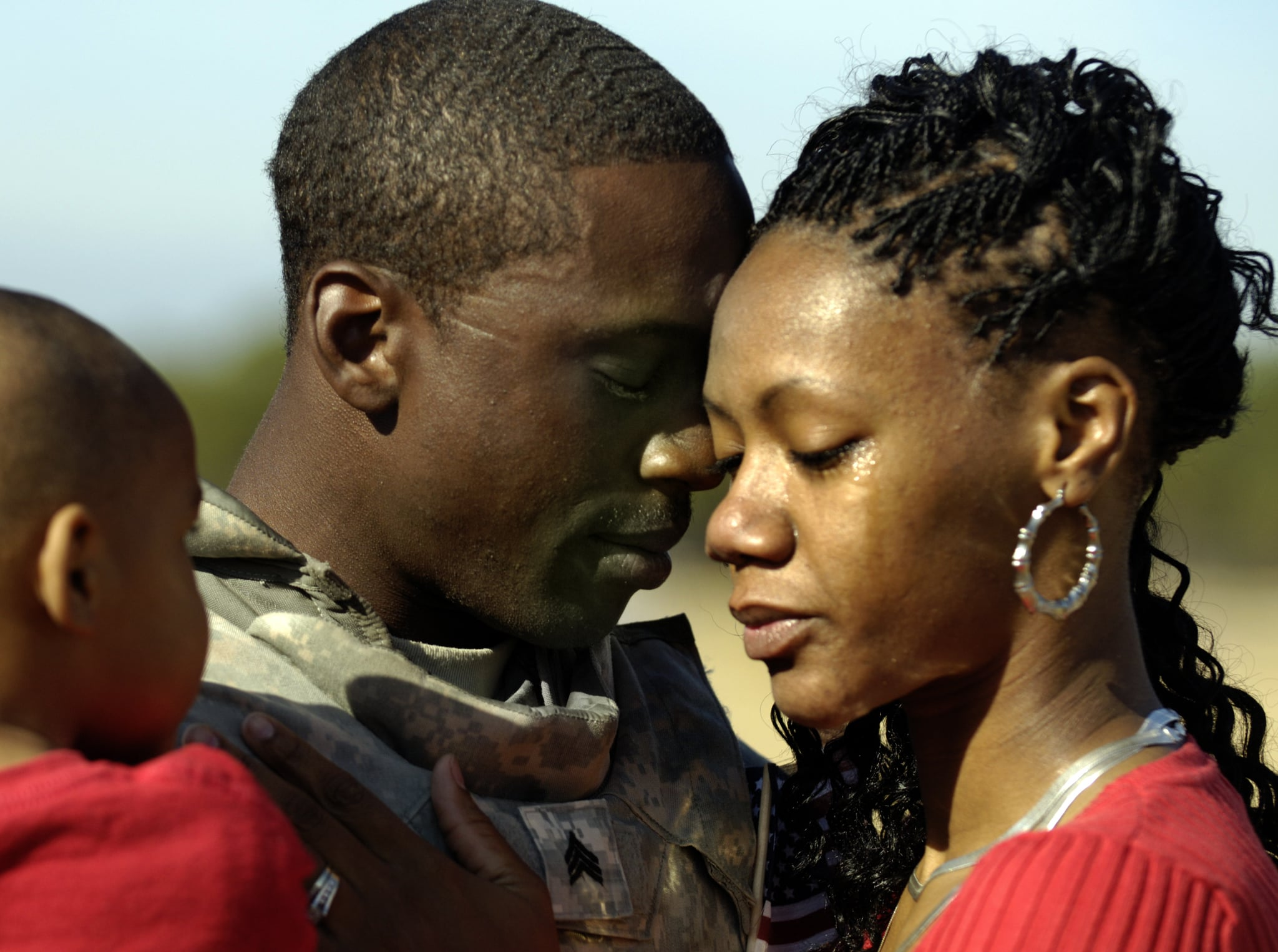 US Army Sgt. Jatorrio Brooks holds his wife, Stephanie, and son, TyReeq, during a homecoming ceremony in 2008.
