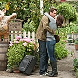Violet embracing her man in jeans, a striped tee, a gray cardigan, and boots.
