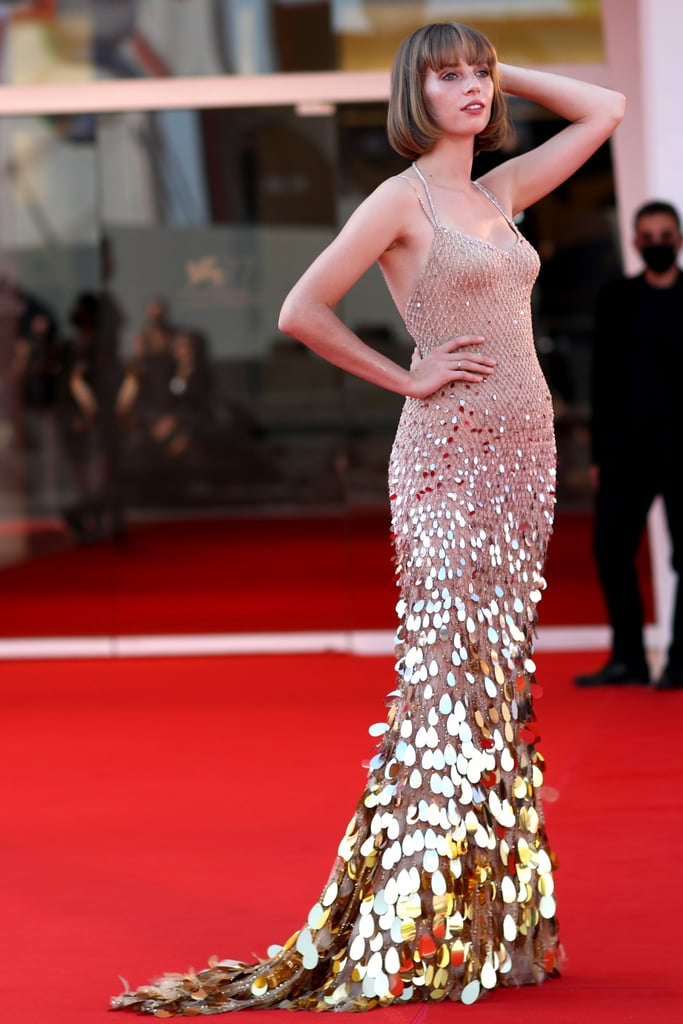 Maya Hawke brought the glittering gold magic to the 77th Venice Film Festival red carpet on Sept. 5. The 22-year-old actress showed up for the socially distanced event to promote her latest film, Mainstream, and boy, did she dress to impress. Maya chose a mermaid-style Versace gown embellished with embroidered Swarovski crystals and lustrous gold-tone appliqué for the occasion.  Like most of the film festival's participants, Maya accessorized her outfit with a complementary mask. She chose a matching face covering with a blush sheen — perhaps a nod to her recently released debut album? We like to think so. Get a closer glimpse at her elegant ensemble ahead.