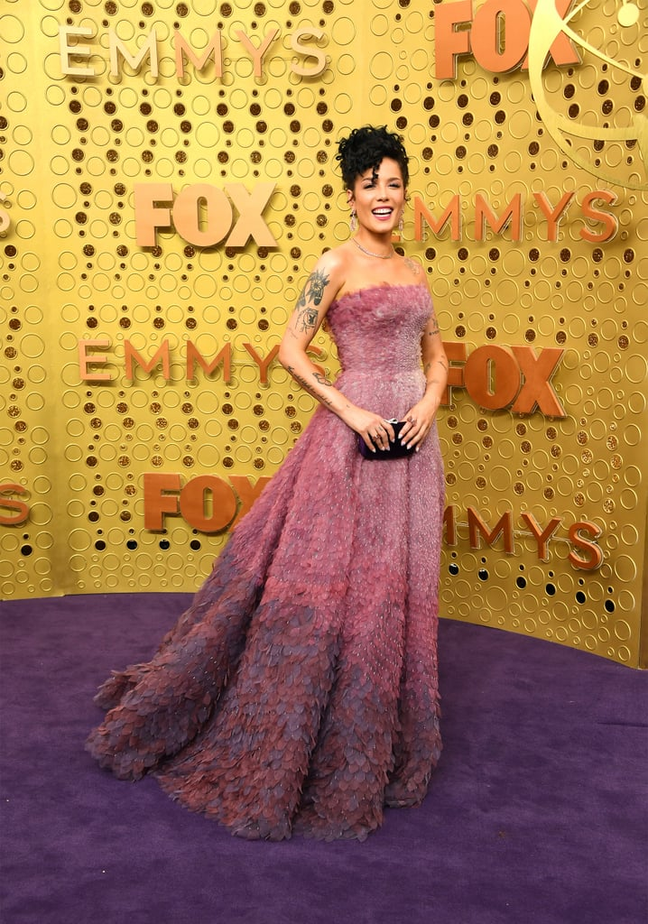"""Halsey looked like a real-life princess when she stepped out at the 2019 Emmy Awards in LA on Sunday night. Dressed in a gorgeous pink and purple gown, the 24-year-old singer was practically glowing as she marked her first time at the ceremony. While Halsey wasn't nominated for any awards, she delivered an emotional cover of """"Time After Time"""" during the in memoriam segment.  Halsey's big night comes a little over a week after she attended Rihanna's Savage x Fenty show in NYC, where she avoided a potentially awkward run in with her ex G-Eazy. She also performed at the iHeartRadio Music Festival in Las Vegas on Friday night and recently released her new single, """"Graveyard."""" Yep, it's definitely been a busy month for Halsey. See more of her glamorous Emmys night ahead!       Related:                                                                                                           These Hot Halsey Pictures Will Have You Working Up a Sweat"""