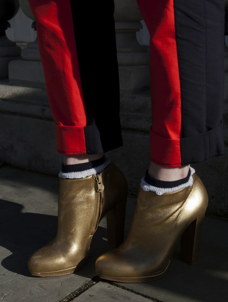 Gold ankle boots and red trousers stood out against the street-style crowd.