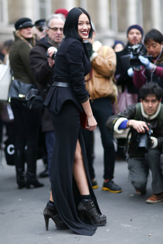 A dramatic arrival in a slit floor-length skirt, peplum-trimmed jacket, and tough-girl ankle boots.