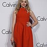 Chloe Moretz lit up the carpet in an orange dress at the Calvin Klein Collections event.