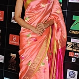 Wearing a pink embroidered sari.