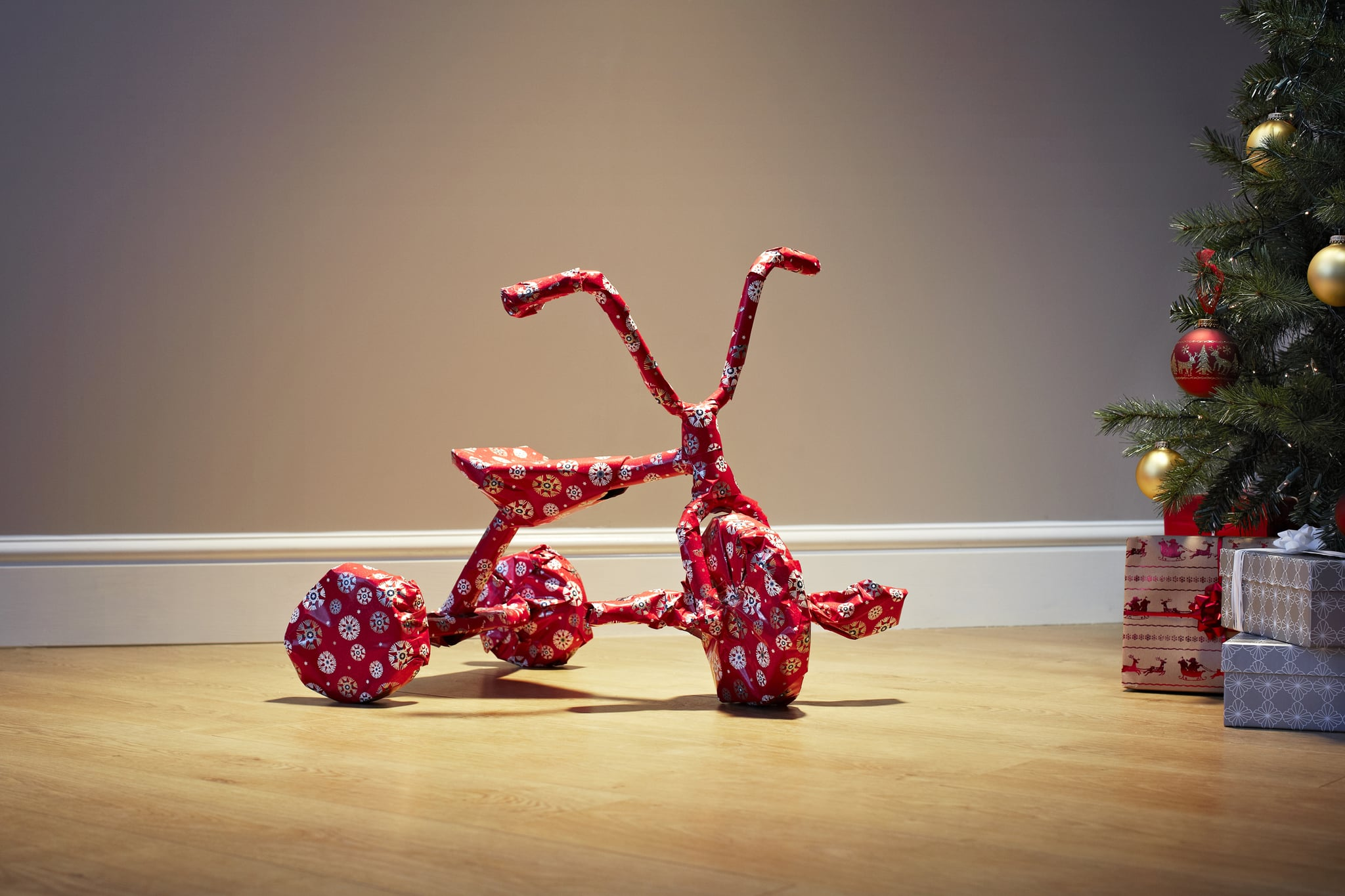 Child's bicycle wrapped in Christmas paper on floor next to christmas tree and presents