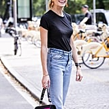 Playful earrings and a designer bag take a simple tee-and-jeans pairing to the next level.