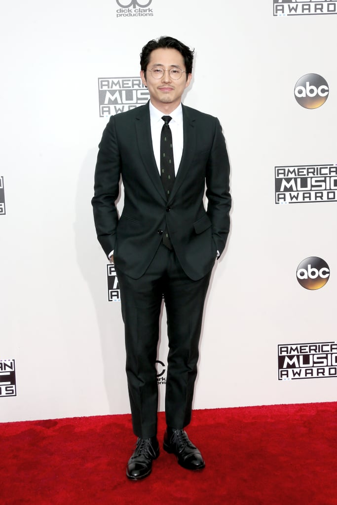 Steven Yeun took a break from gluing his skull back together to enjoy a glitzy night out at the American Music Awards on Sunday. The former star of The Walking Dead hit the red carpet looking bookish and sexy in a pair of glasses and a sharp suit, proving yet again that the cast of the zombie drama sure cleans up nice. Following his brutal exit from AMC's hit show, Steven recently attended a Clippers game with wife Joanna Pak and chose to sell his gorgeous Hollywood home. We're still not over the fact he's officially gone from The Walking Dead, but we have to admit that outings like these are definitely helping to ease our Glenn withdrawals.