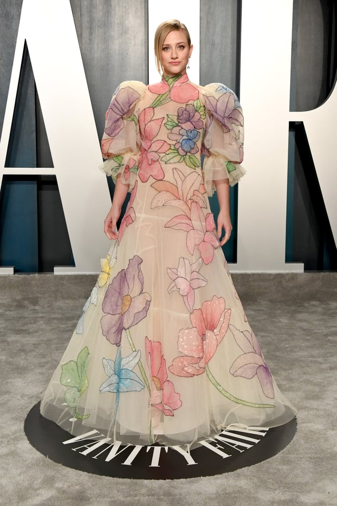 Nothing makes us smile more than Lili Reinhart's joyful dress at the Vanity Fair Oscars afterparty. The voluminous floral gown features dramatic puff-sleeves and pastel embroidery fit for a princess. Reinhart complemented her look with blue drop earrings and a classic updo. The contrast of colorful flowers against her beige dress is so lovely. Don't you think it's time she stars in a movie as royalty? This elegant look has us totally convinced. Make sure to look at all the detailed photos of her dazzling ensemble. All she needs is a crown!