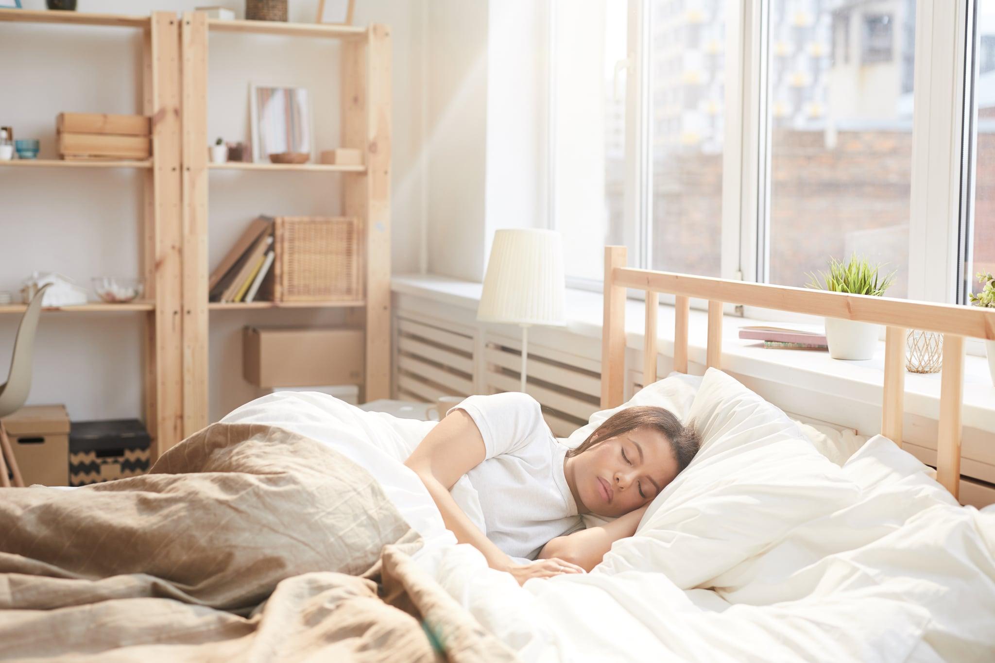 Portrait of beautiful Mixed-Race woman sleeping in bed in sunlit bedroom, copy space