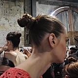 """We're trying to create a look that doesn't feel laboured, but establishing enough texture to be able to pull it into a ponytail. It's still feeling quite raw, allowing for natural texture to pull it around [into a bun] with a silicone elastic,"" she says."