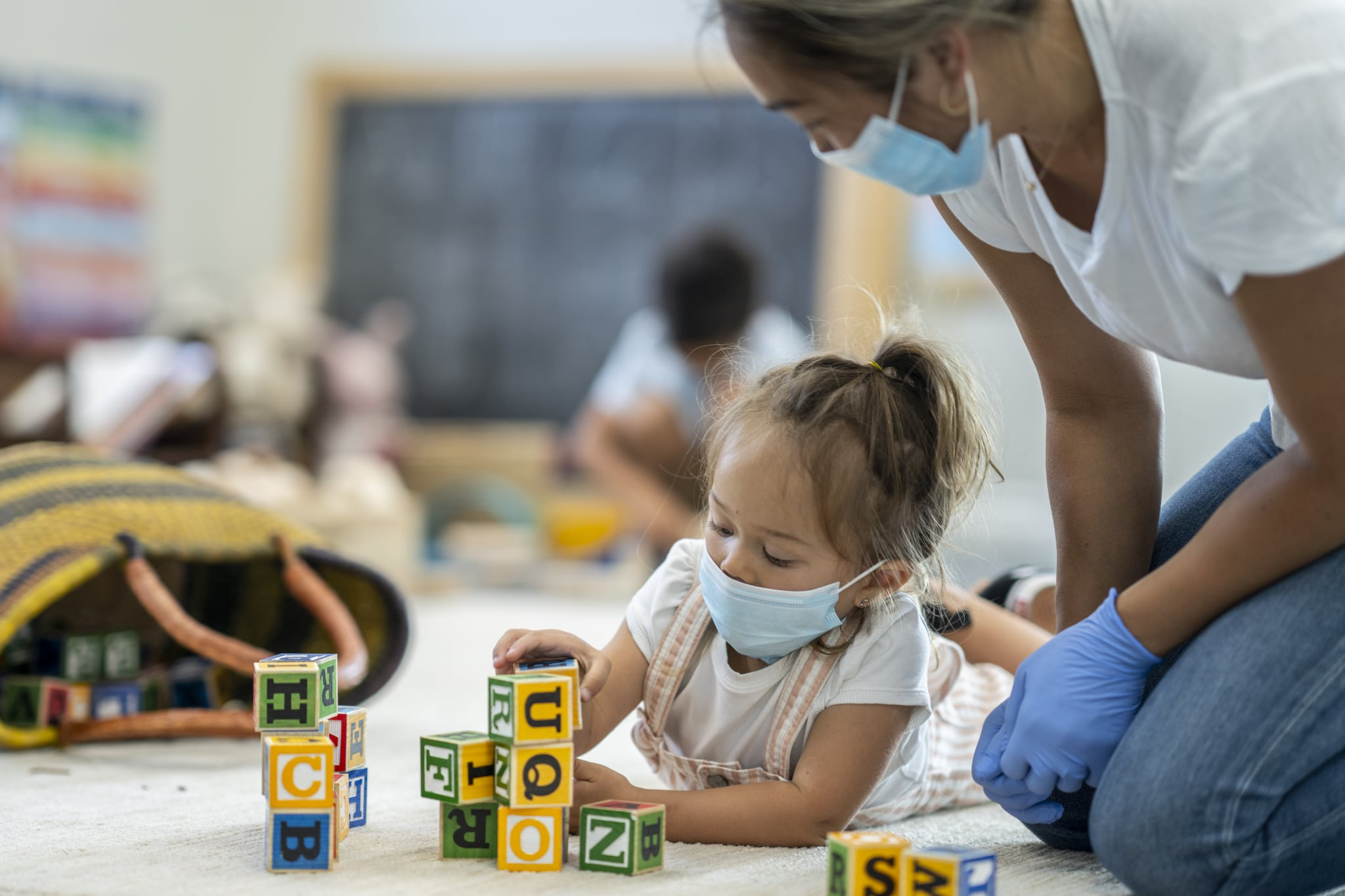 3 year old girl playing at daycare while wearing a protective face mask to protect from the transfer of germs during phase 2 of reopening during COVID-19.