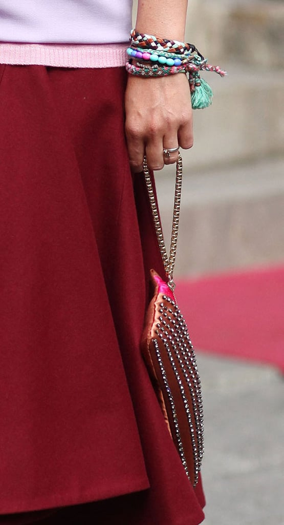 A wristful of colored bracelets was a subtle accent against a classic skirt — as was a studded clutch. Source: Greg Kessler