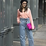 Style with high-waisted jeans, a pastel cardigan, and bright accessories.
