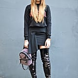 If you think you can't wear over-the-knee boots, think again. Street-style superstar Kristina Bazan pulled off the look like a pro. She opted for a monochrome look and styled a pair of patent leather boots with a sweater and asymmetrical skirt.