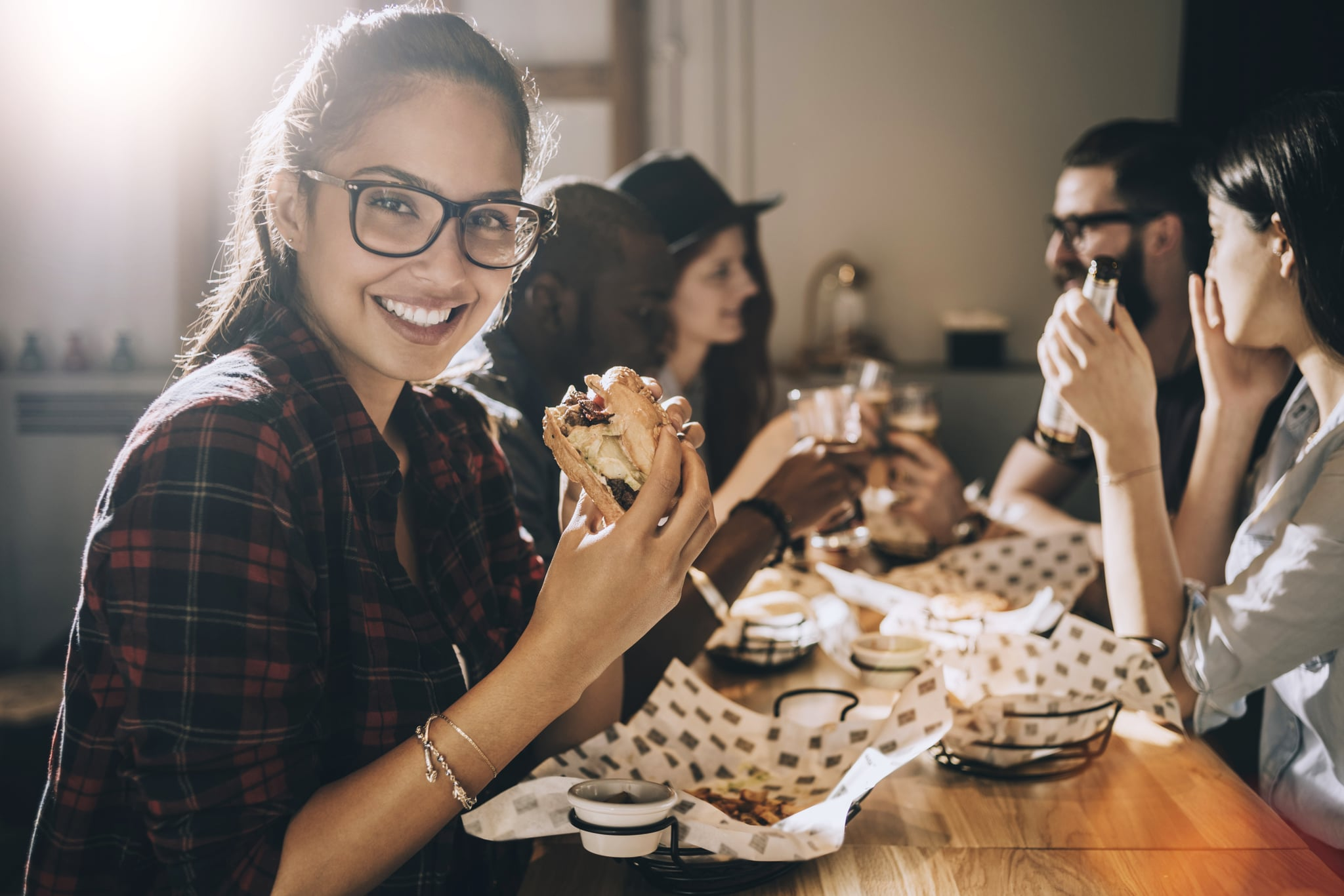 smiling beautiful woman eating a burger and having fun with her friends