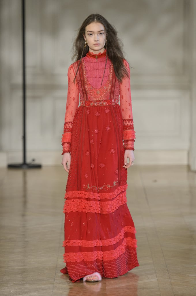 The next time you can't decide what to wear, look back at Valentino's Fall 2017 collection. Creative Director Pierpaolo Piccioli created the ultimate go-to uniform: shift dress with patent leather boots. Easy, right?  The designer sent billowy long-sleeved dresses in shades of red, blush, teal, and chartreuse down the runway, and every model wore an identical red beaded necklace. Boots were the shoe of choice, partly concealed underneath the hem of these everyday gowns. It's clear Piccioli has a penchant for romanticism, a quality the fashion house embodies, as almost every garment in the collection featured a high-neck collar and soft, lace details. Though the Victorian-style dresses were impressively beautiful, the outerwear also shouldn't be missed. Coats with split panels flowed away to reveal silky trousers and patterned dresses underneath. Several of these pieces featured abstract hand prints with mathematical equations. It was a funky design for the fashion house, though the pastel colors stayed true to the collection's aesthetics.  For the girl who loves black, however, do not worry, because Piccioli covered his bases by offering a mix of dark sheer and silky gowns (paired with boots of course) that were delightfully delicate.