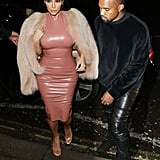 Kim suited up in latex in London, but Kanye played it cool.