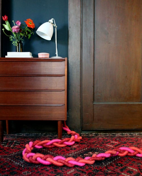 Sometimes, even rugs can't disguise those thick cords that are hideous but absolutely necessary. Instead of making futile attempts to hide them, let them take center stage with bright yarn and plastic cord tubes.  Source: Design*Sponge