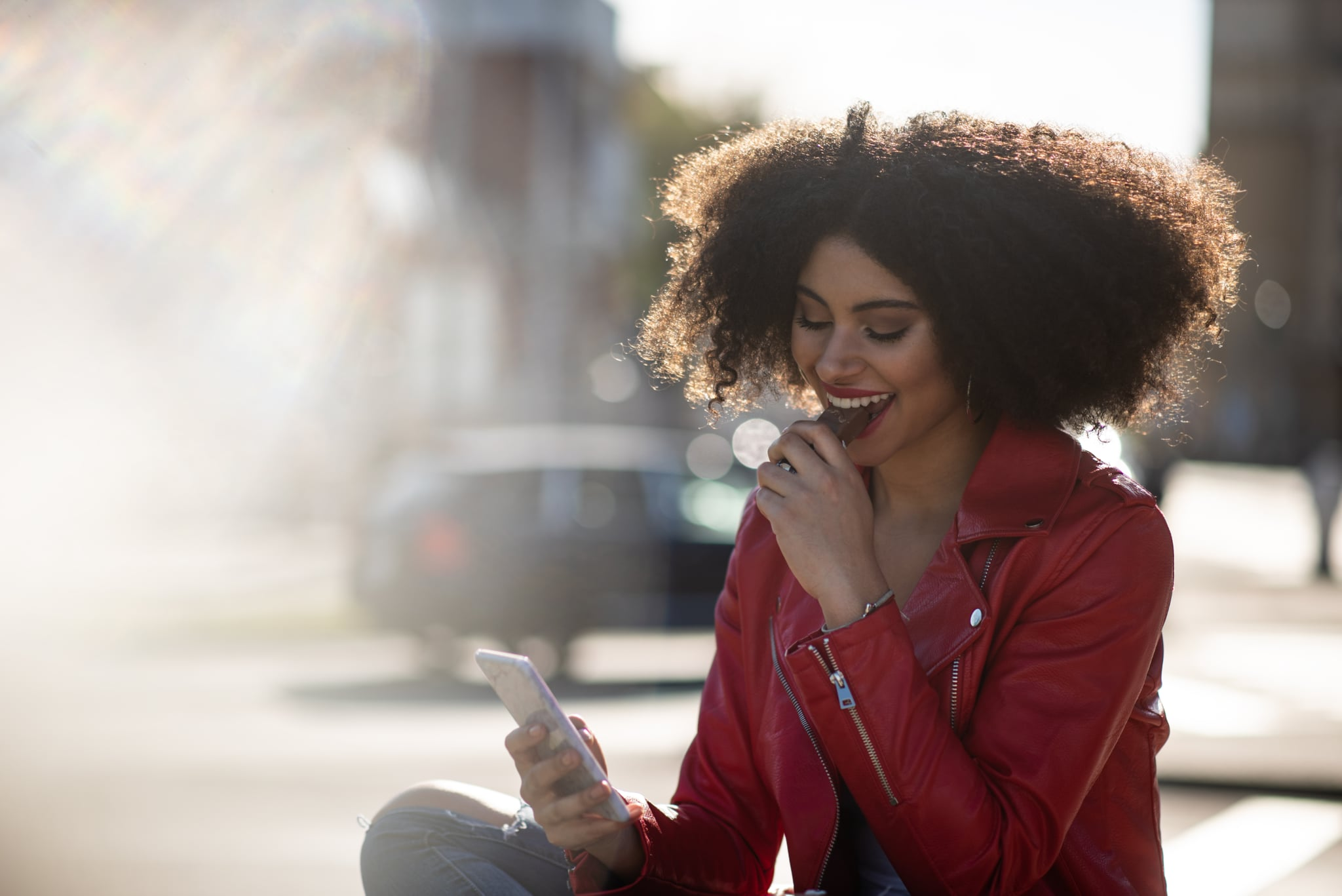 Smiling teen black curly hair girl looking to phone and eating chocolate snack in sunny street